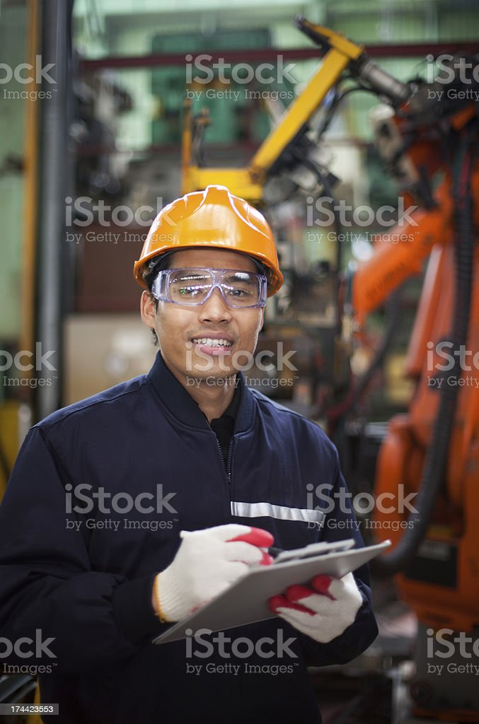 Young man in hard hat writing on clipboard in factory royalty-free stock photo