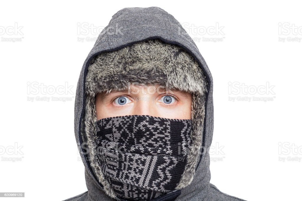 Young man in hat, scarf and hood hiding from weather stock photo
