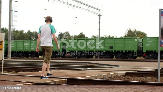 A young man in headphones crosses the railway tracks and listens to music, does not hear the approaching train, security breach on the railway