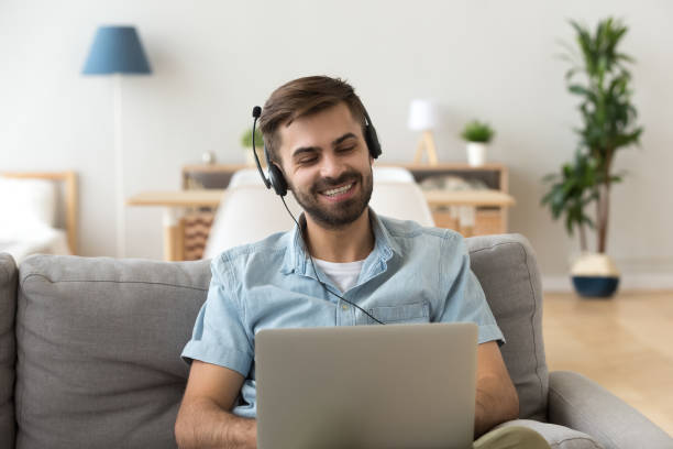 Young man in headset sitting on couch looking at laptop Young happy man in headset sitting on couch at home looking at laptop studying online using computer, friendly guy watching webinar video, learning foreign language training, distance work education only young men stock pictures, royalty-free photos & images