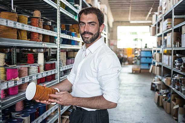 junger mann in seinem meisterhafte handwerkskunst traditionellen textilfabrik - stoffregal stock-fotos und bilder