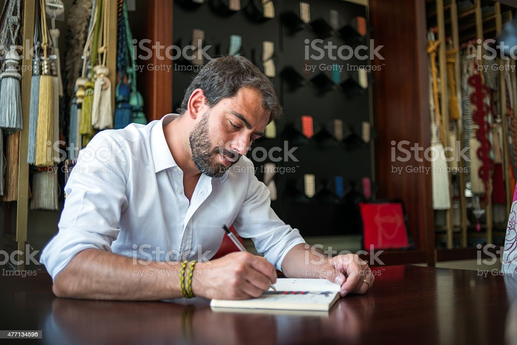 Young man in his artisanal handicraft traditional textile factory stock photo