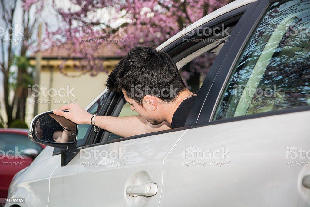 Jovem no carro, ajustando espelho retrovisor - foto de acervo