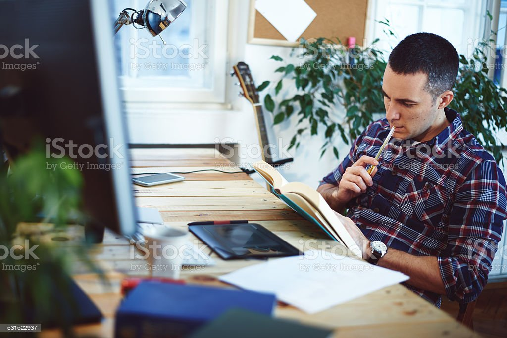 Young man in home office reading book stock photo