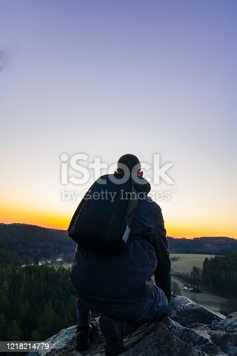 Young man in jacket, pants and backpack sitting on rock looking to valley at sunrise.