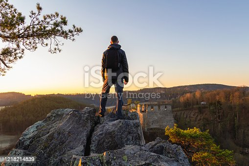Young man in jacket, pants and backpack standing and looking to ruin Divci kamen from rock. Czech republic