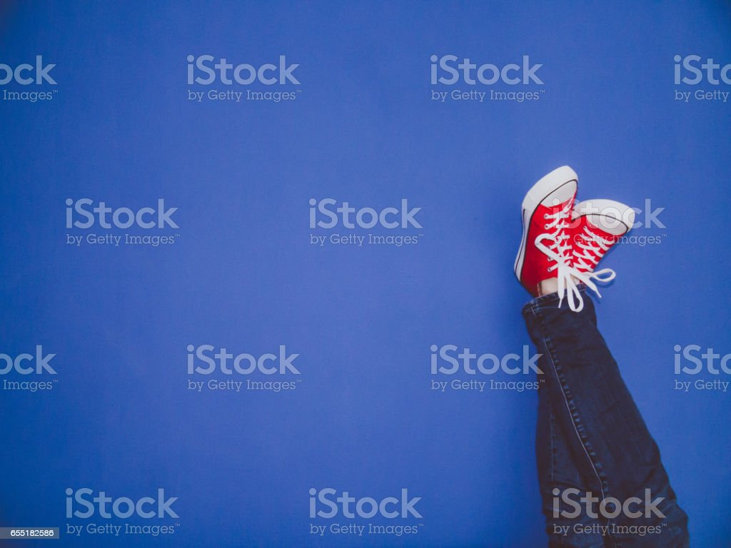 Young man in jeans and red sneakers with his feet against the blue wall. stock photo