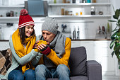 istock young man in knitted hat, scarf and gloves warming hands of freezing girlfriend 1275775122