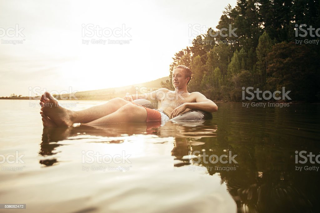 Young man in lake on inflatable ring stock photo