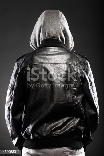 istock Young man in leather jacket and hood rear view 454063311