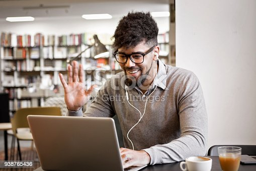 istock Young man in library on laptop drinking coffee 938765436