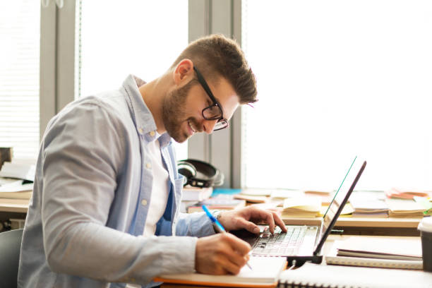 Young man in library on laptop stock photo