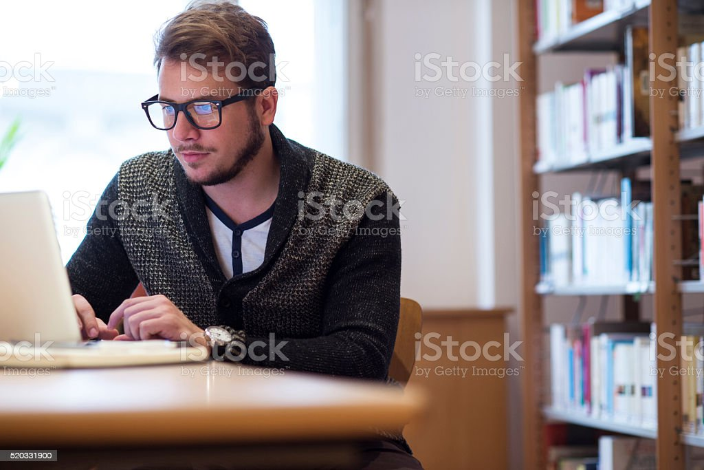 Young man using laptop and studying in library