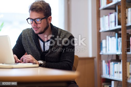 istock Young man in library 520331900