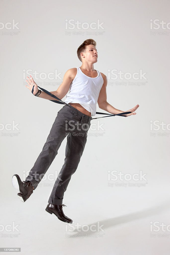 Young man in mid air pulling trouser braces