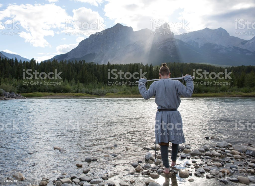 Young man in Norman costume walks into river and looks out to mountains stock photo
