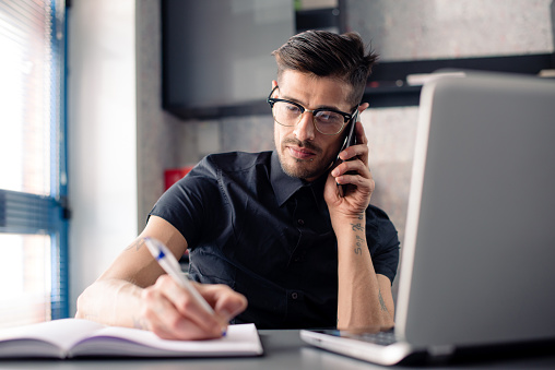 Young man in office working on laptop computer and phone