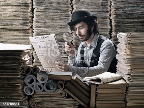 istock Young man in old fashioned costume doing research among newspapers 481258841