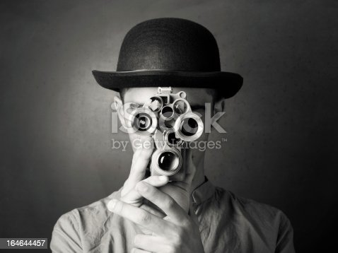 Young man in old fashioned style filming via antique camera.The model is wearing bowler hat.He is holding camera in a position that it covers his face.The lenses of camera give eyes look on face.The photo was shot in studio with a full frame DSLR camera in color then edited to black and white.