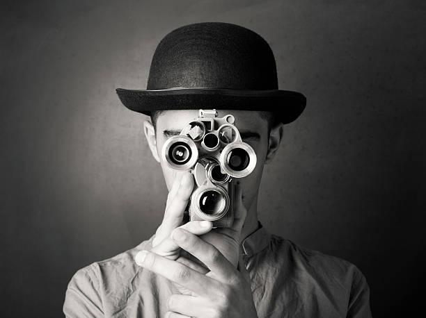 junger mann in alten altmodischen stil filmen über antike kamera - fotografische themen stock-fotos und bilder