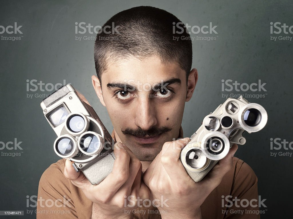 Young man in old fashioned style filming via antique camera royalty-free stock photo