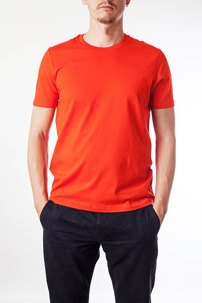 Young man in orange shirt with his hands in his pockets stock photo