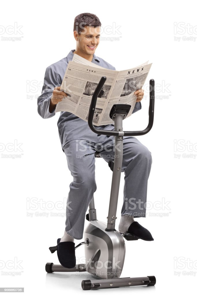 Young man in pajamas reading a newspaper on a stationary bike stock photo