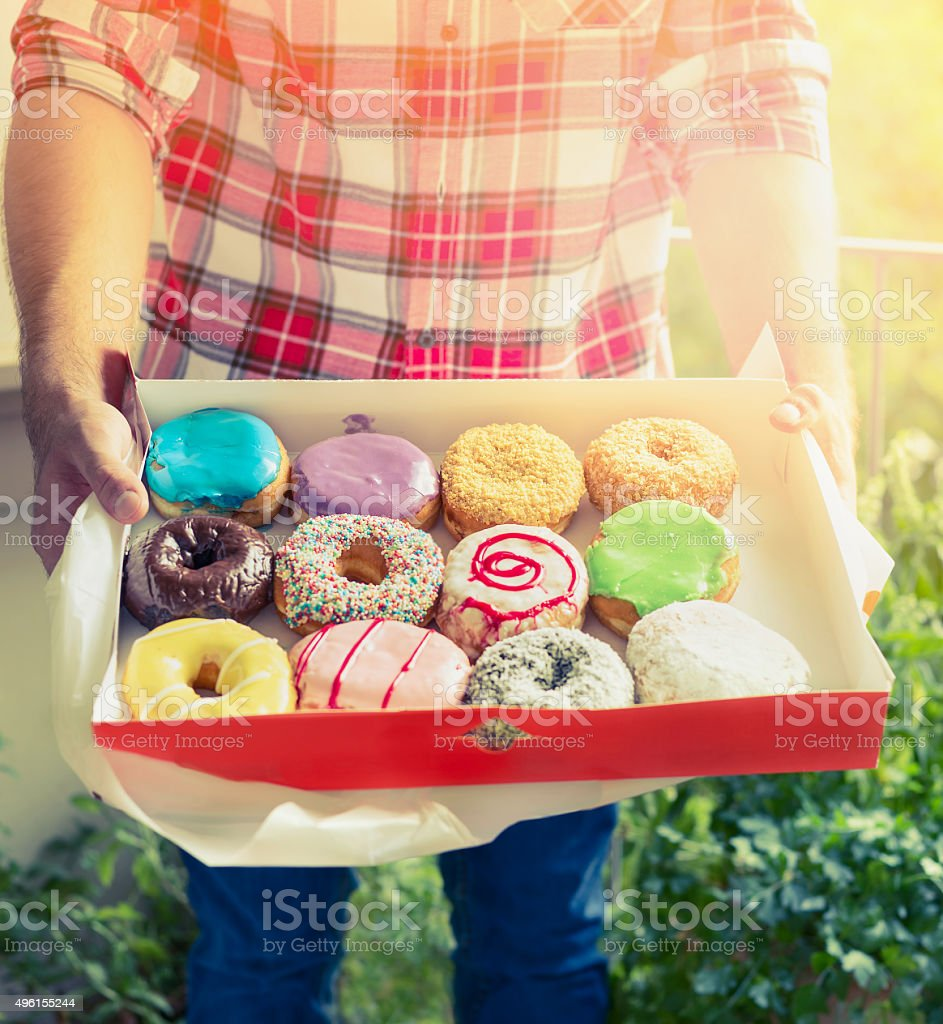 young man in plaid shirt holding colorful glazed donuts stock photo