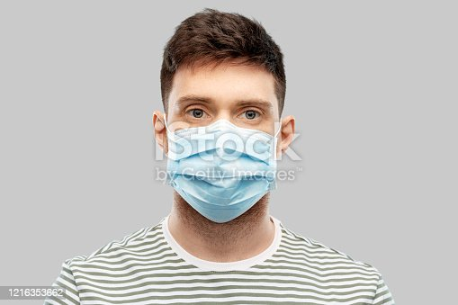 health protection, safety and pandemic concept - young man in protective medical mask over grey background