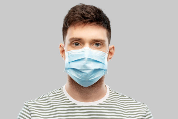 young man in protective medical mask stock photo