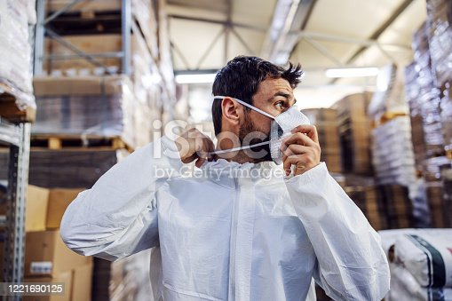 Young man in protective suit putting face mask and preparing himself for disinfection from corona virus / covid-19. Warehouse interior. Warehouse is full of food products.