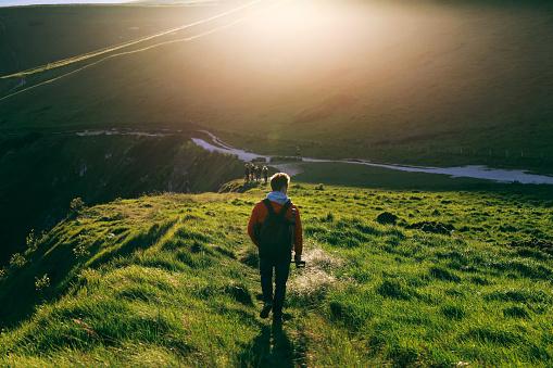 Young man in red jacket walking on a path towards Durdle Door alongside Jurassic Coast, Dorset, UK