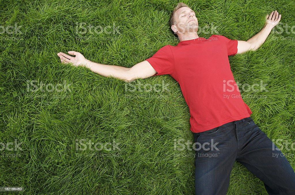 Young Man in Red T-Shirt Relaxing on Green Grass stock photo