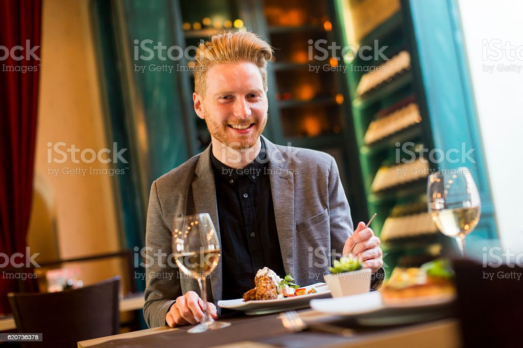 Young man in restaurant - Royaltyfri Banta Bildbanksbilder