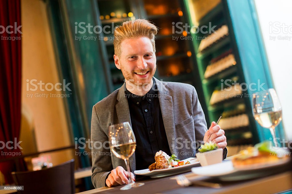 Young man in restaurant - Royaltyfri Banta Bildbanksbilder