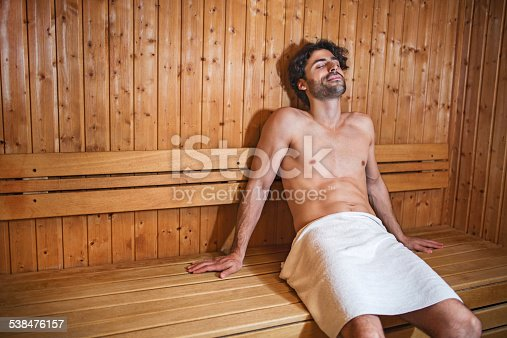 Young man enjoying in sauna with his eyes closed.