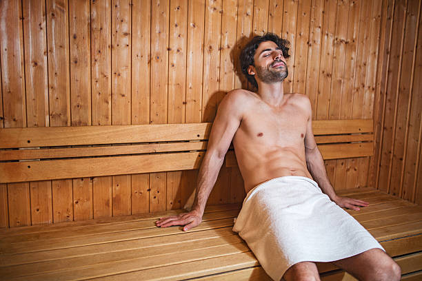 Young man in sauna. Young man enjoying in sauna with his eyes closed. sauna stock pictures, royalty-free photos & images