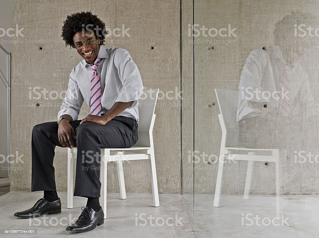 Young man in shirt and tie smiling on chair near window, portrait photo libre de droits
