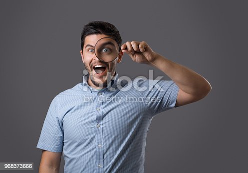 istock Young man in shirt with magnifying glass 968373666
