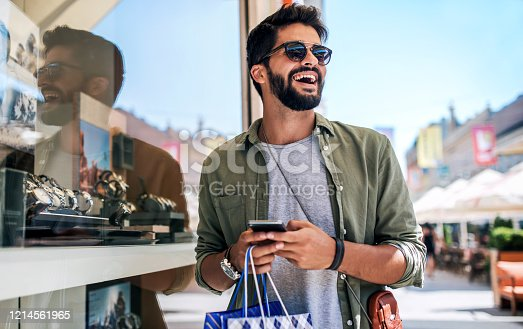 istock Young man in shopping looking for presents. Consumerism, fashion, lifestyle concept 1214561965
