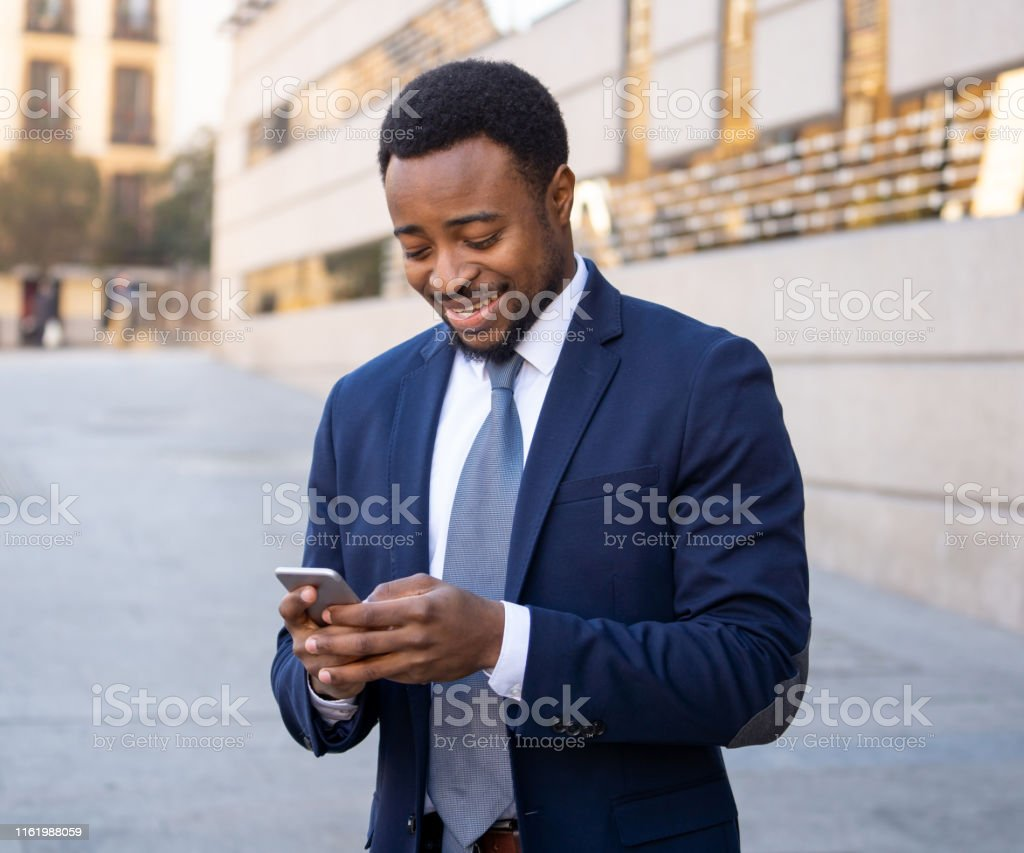 Young man in smart wear on mobile phone sending text email or social...