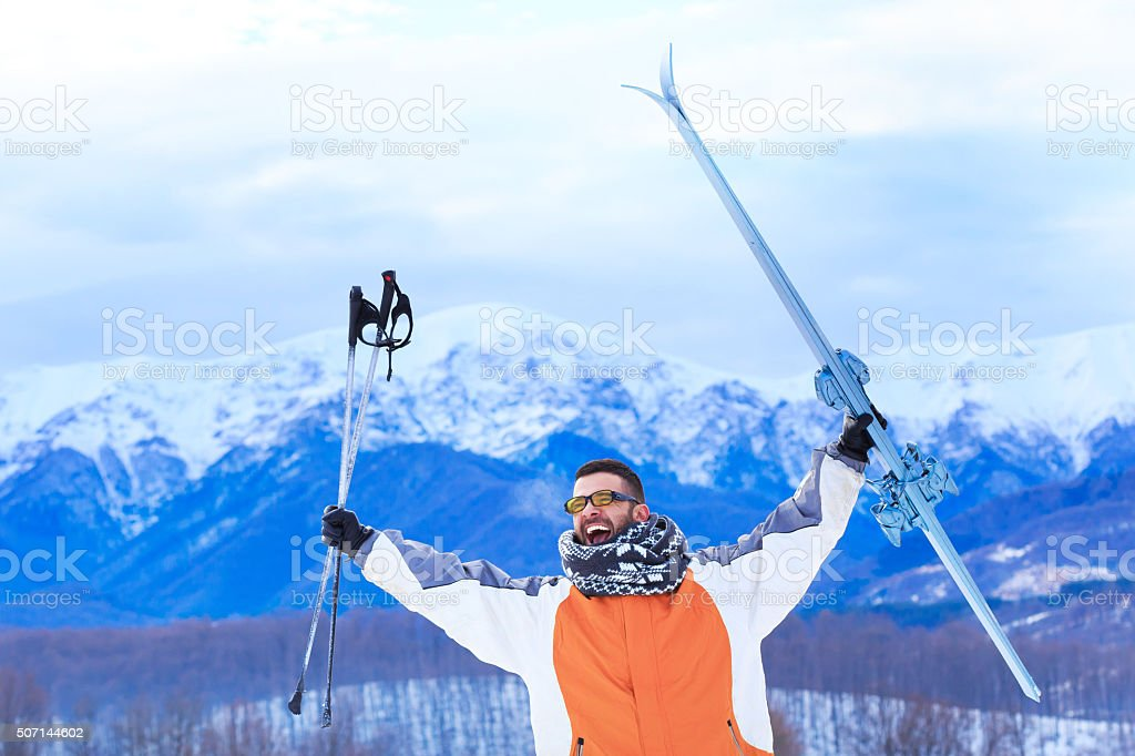 Young man in snow mountain-hands up holding ski and poles stock photo