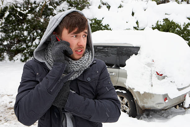 Young man in snow with broken down car stock photo