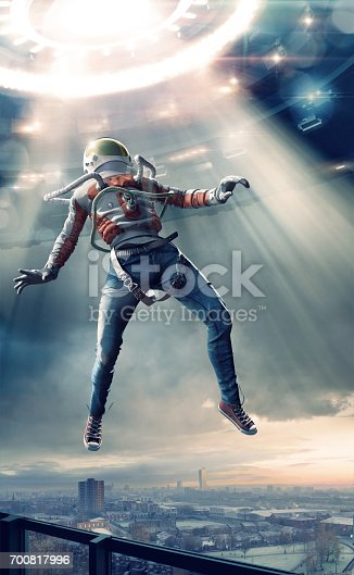 istock Young Man in Spacesuit Levitating in Light Towards UFO 700817996