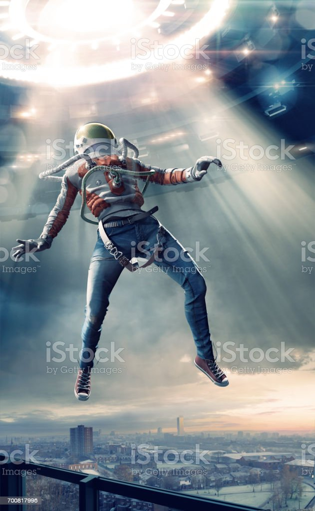 Young Man in Spacesuit Levitating in Light Towards UFO stock photo