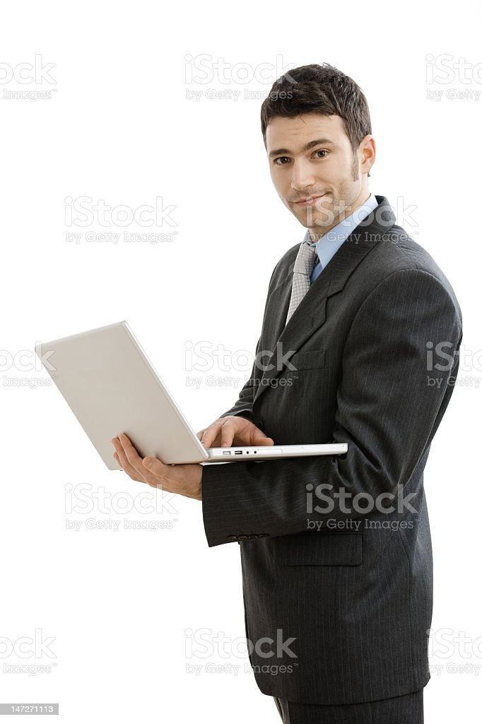Young man in suit holding silver laptop and white background royalty-free stock photo