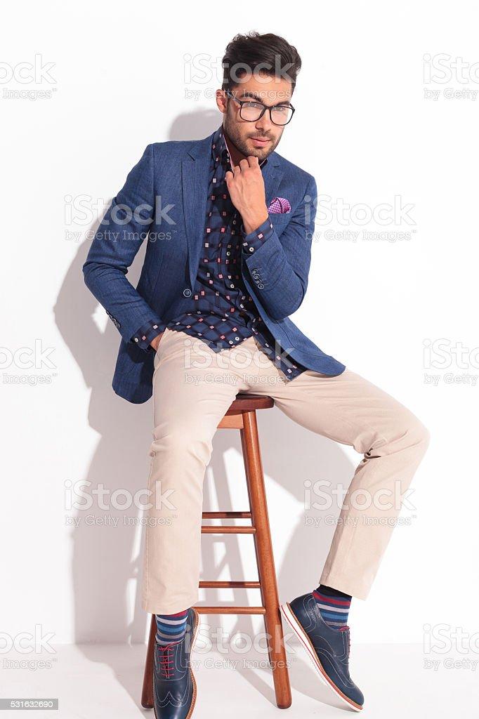 ac4b7fd7cf71e Hombre joven en traje de pensar mientras está sentado sobre una silla foto  de stock libre