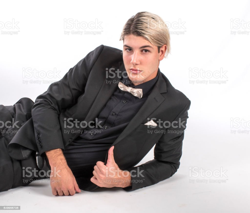 Young man in suit on floor gives 'thumbs up' sign stock photo