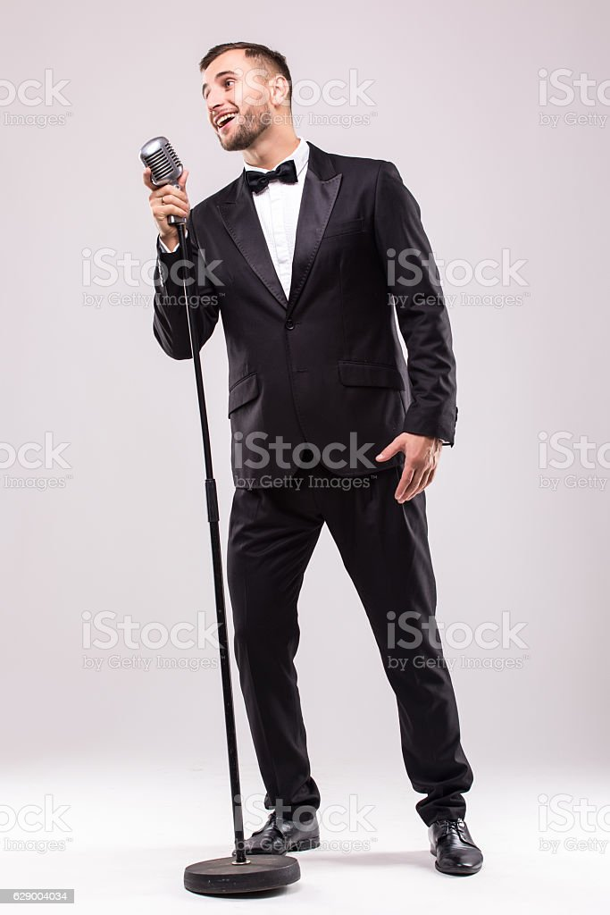 Young man in suit singing over the microphone with energy. stock photo