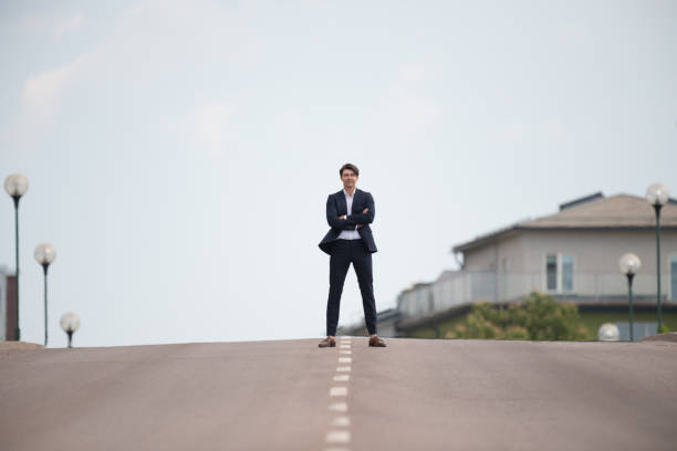 Young man in suit, standing confident in the middle of the road Young man in suit, standing confident in the middle of the road middle of the road stock pictures, royalty-free photos & images